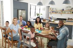 Two families having lunch together at home looking to camera stock photos