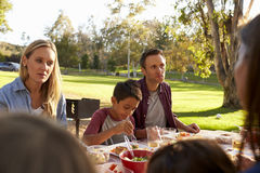 Two families having a picnic in a park, over shoulder view Stock Photos