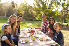 Two families having a picnic at a table look to camera Stock Photo