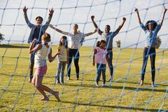 Two families playing football in park cheering the girl royalty free stock photo