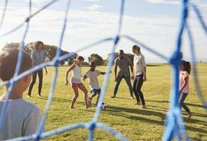 Two families playing football in park seen through goal net Stock Photo