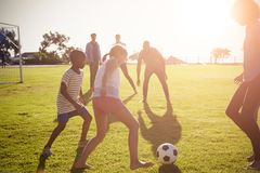 Two families playing football in a park Stock Photography