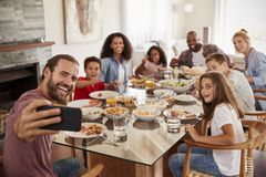 Two Families Taking Selfie As They Enjoy Meal At Home Together stock photos
