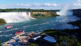 Two famous waterfalls of Niagara Falls with tourist boats. View of the two famous waterfalls of Niagara Falls with tourist boats stock video footage