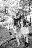 Two fanny and cheerful twins girls playing the ape on the camera. Girl make quaver faces and show the tongue. Sisters. Outdoor. Happiness. Black and white stock photography