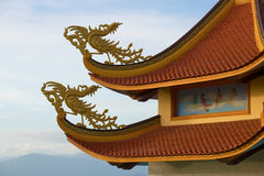 Two fantastic roosters on a roof of the Buddhist temple against the background of the cloudy sky, Phan Thiet. Vietnam Royalty Free Stock Photo