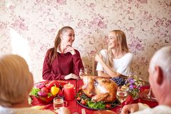 Happy sisters at the family festive Thanksgiving dinner on a light background. Domestic celebrating concept. royalty free stock photos
