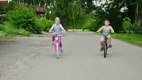 Two farm children are riding bicycles in the countryside. Steadicam shot stock footage