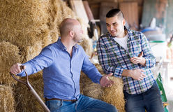 Two farm workers in hayloft Stock Photo
