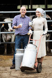 Two farmer workers in cowshed Royalty Free Stock Photography