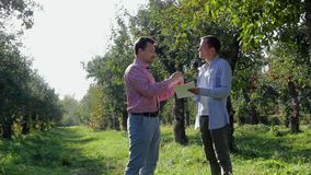 Two farmers conclude an agreement in the apple orchard. A pair of rural businessmen sign papers and shake hands on a background of green trees stock footage