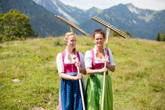 Two farmers in dirndl with rakes in an alpine meadow. On the way to work - Waist Up, horizontal Royalty Free Stock Photography