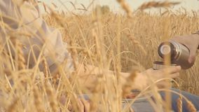Two farmers having lunch in a golden wheat field eating sandwich slow motion. Two farmers having lunch in a golden wheat field drinking tea slow motion stock video footage