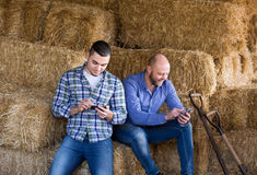 Two farmers with phones at hayloft Stock Photos