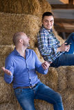 Two farmers with phones at hayloft Stock Photo