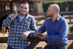 Two farmers with phones Stock Image