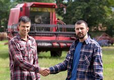 Farmers shaking hands in front of combine harvester Stock Photos