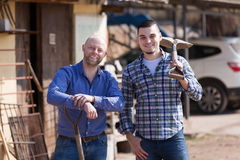 Two farmers standing with spades. Two happy male farmers standing with spades at farmyard Stock Images