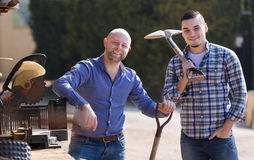 Two farmers standing with spades. Two male farmers standing with spades at farmyard Stock Photo