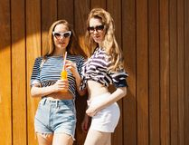 Two fashion beautiful girls in the marine clothing, shorts, stylish sunglasses standing near a wall of wooden planks. Drink a cool Royalty Free Stock Photo