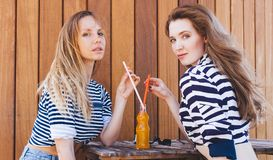 Two fashion beautiful girls sitting in a summer cafe and drink orange beverage through a straw from a bottle. Sunny warm summer da Stock Images
