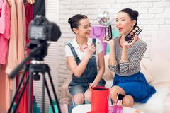 Two fashion blogger girls hold up brushes and eye shadows to camera. Two fashion blogger girls in jeans and shirt with skirt hold up brushes and eye shadows to royalty free stock image
