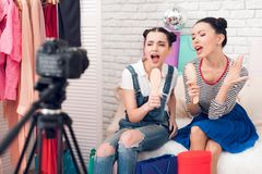 Two fashion blogger girls hold up combs singing to camera. Two fashion blogger girls in jeans and shirt with skirt hold up combs singing to camera Royalty Free Stock Photo