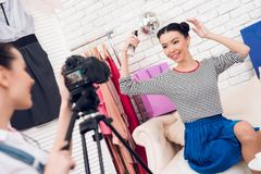 Two fashion blogger girls hold up hair spray with one girl behind camera. stock photography