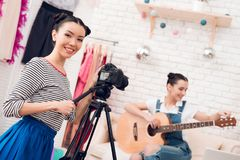 Two fashion blogger girls play guitar with one girl behind camera. royalty free stock photo