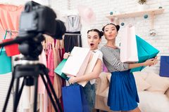 Two fashion blogger girls present many colorful bags to camera. royalty free stock photo