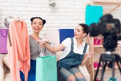 Two fashion blogger girls point at colorful dress to camera. stock image