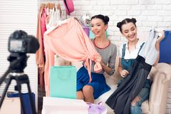 Two fashion blogger girls pull colorful dress from colorful bags to camera. Two fashion blogger girls in jeans and shirt with skirt pull colorful dress from Royalty Free Stock Image