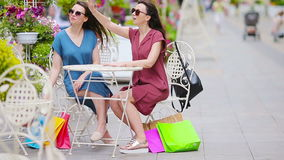 Two fashion colorful shoppers with bags shopping in openair cafe. Sale, consumerism and people concept. Caucasian girls. Two fashion colorful shoppers with bags stock footage