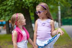 Two fashion cute sisters go hand in hand in the Royalty Free Stock Photos