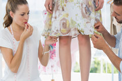 Two fashion designers adjusting dress on model. In the studio Royalty Free Stock Photos