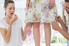 Two fashion designers adjusting dress on model Royalty Free Stock Photos