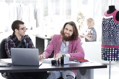 Two fashion designers discussing designs of the new models royalty free stock image