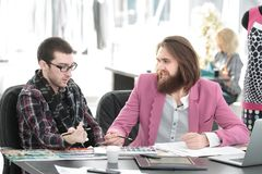Two fashion designers discussing designs of the new models stock photo