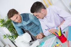 Two fashion designers using sewing machine in studio. Two fashion designers using sewing machine in a studio Stock Image