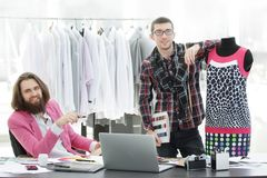 Two fashion designers are working on creating women`s clothing in the Studio stock image