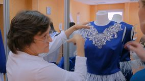 Two fashion designers working with new model tailoring dress on mannequin. Two professional tailors, designers working with new model tailoring dress on stock video footage
