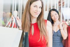 Two fashion girlfriends shopping at mall Royalty Free Stock Image