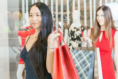 Two fashion girlfriends shopping at mall Stock Images