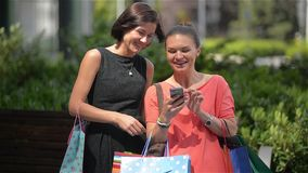 Two fashion girls with bags shopping with a smart phone in the street, beautiful woman using telephone. Laugh stock footage