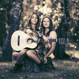 Two fashion girls with guitar in a summer forest Royalty Free Stock Photography