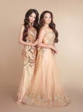 Two fashion ladies. Beautiful women with wavy hair wears in long Royalty Free Stock Images