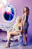 Two fashion models posing in glamorous interior Royalty Free Stock Photos