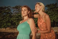 Two fashion models posing in red and turquoise dresses in the rays of the setting sun on a tropical beach stock photos