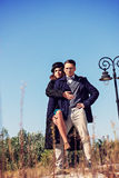 Two fashion people in vintage style posing in below shot. Woman wearing winter coat and hat standing with lifted leg next to male model, Couple in fashion Royalty Free Stock Image