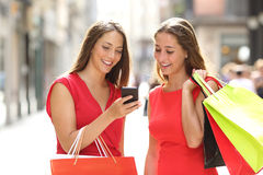 Two fashion shoppers shopping with a smart phone. Two fashion colorful shoppers with bags shopping with a smart phone in the street royalty free stock photos